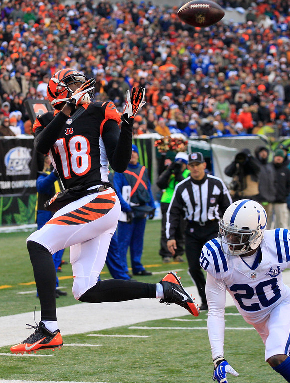 . Cincinnati Bengals wide receiver A.J. Green (18) catches a 9-yard touchdown pass against Indianapolis Colts free safety Darius Butler (20) in the second half of an NFL football game, Sunday, Dec. 8, 2013, in Cincinnati. (AP Photo/Tom Uhlman)