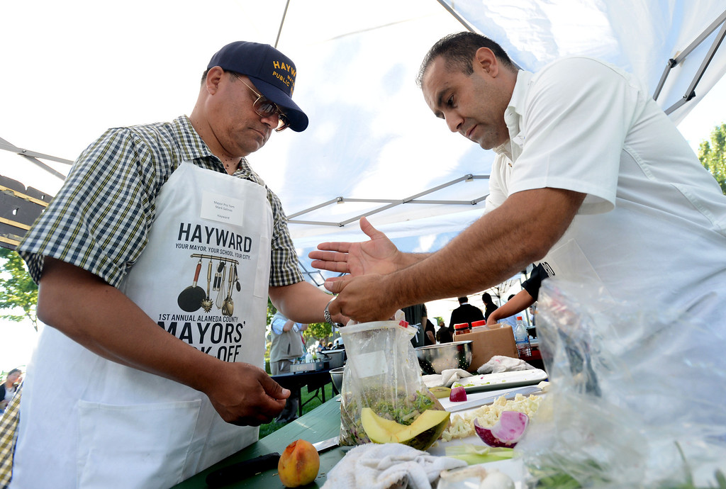 ". Hayward Mayor Pro Tem Mark Salinas, left, and Chef Tony Solorio with the Hayward\'s Tacos Uruapan restaurant prepare a chicken marinade during the ""Alameda County Mayors\' Healthy Cook-Off Challenge\"" held at the Dublin Farmers\' Market at Emerald Glen Park in Dublin, Calif., on Thursday, July 25, 2013. The Hayward team went on to place second, advancing them to compete against the winners of the Contra Cost County Mayors\' Healthy Cook-Off Challenge. The contest will be held at Mt. Diablo High School in the fall. The cook-off was presented by Concord\'s Wellness City Challenge and promotes the importance of healthy eating. (Doug Duran/Bay Area News Group)"