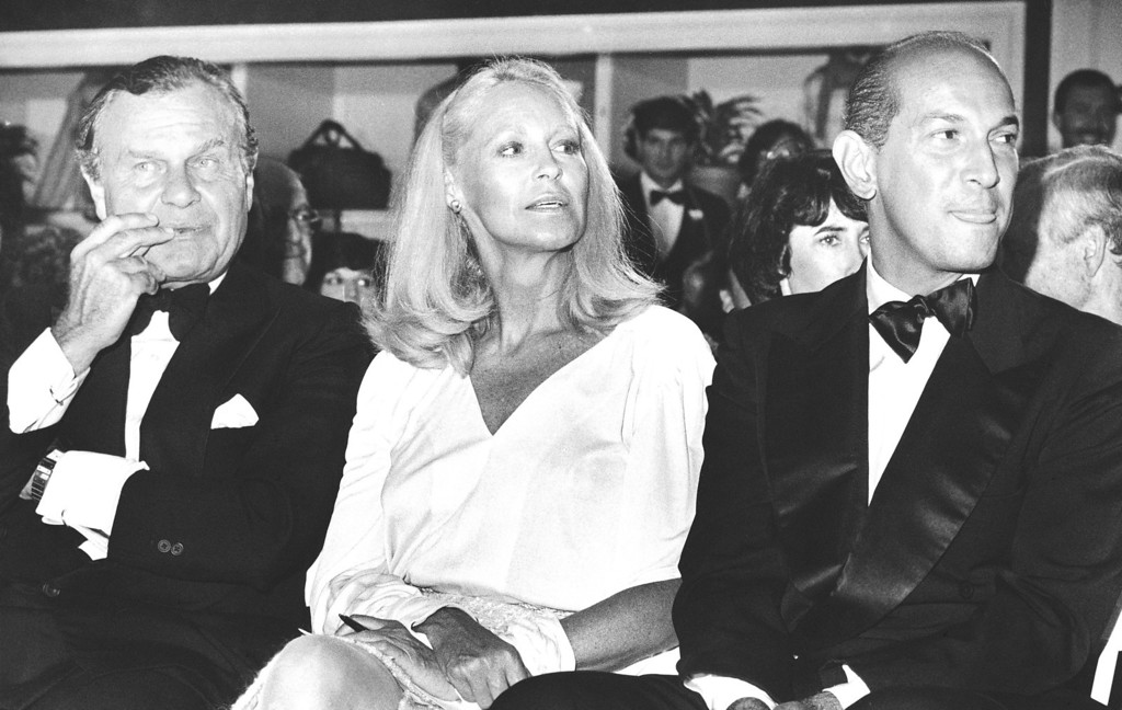 . Joan Bennett Kennedy, center, sits between fashion designers Bill Blass, left, and Oscar de la Renta, right, at a gala fashion show to benefit the Wang Center for the performing arts in Boston on Monday, Sept. 20, 1983. (AP Photo/Keith E. Jacobson)