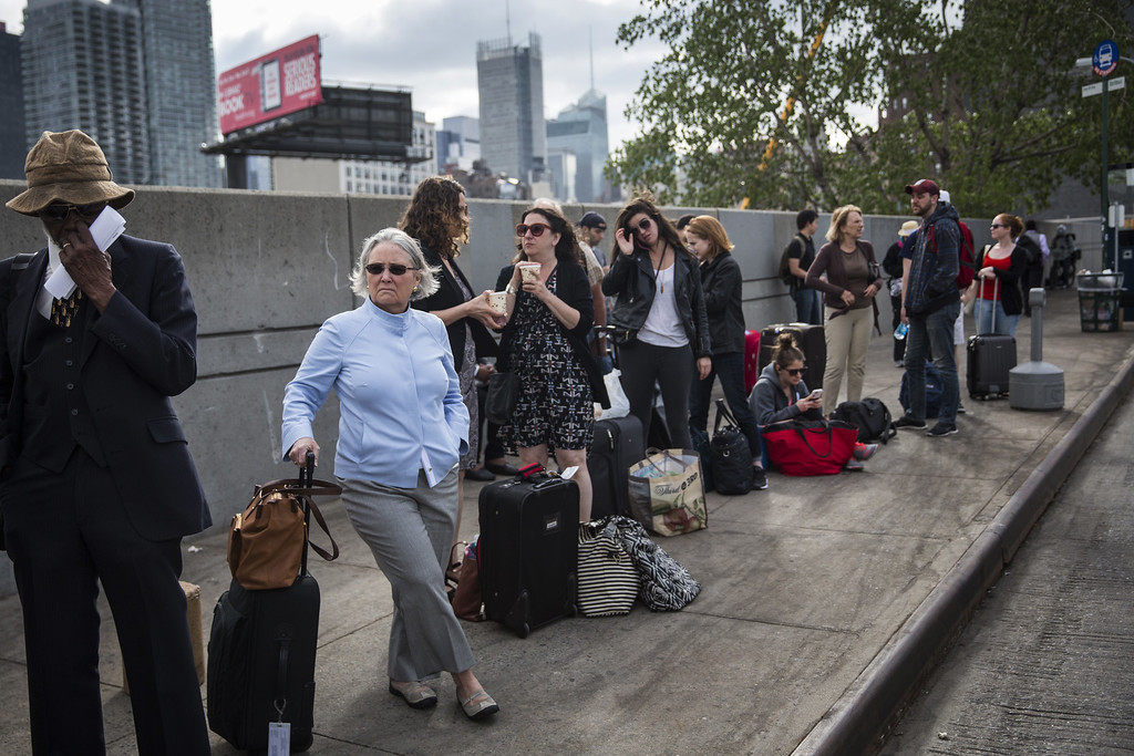 . NEW YORK, NY - MAY 13:  Carolan Berkeley (L), who had an Amtrak ticket to go from New York to Washington D.C., waits for a bus from New York to Washington D.C. on May 13, 2015 in New York City. An Amtrak train crash in Philadelphia last night has forced train service to be suspended between New York, Philadelphia and Washington D.C., causing commuters to use NJ Transit, flights and bus services. The crash killed at least six people and injured dozens more.  (Photo by Andrew Burton/Getty Images)