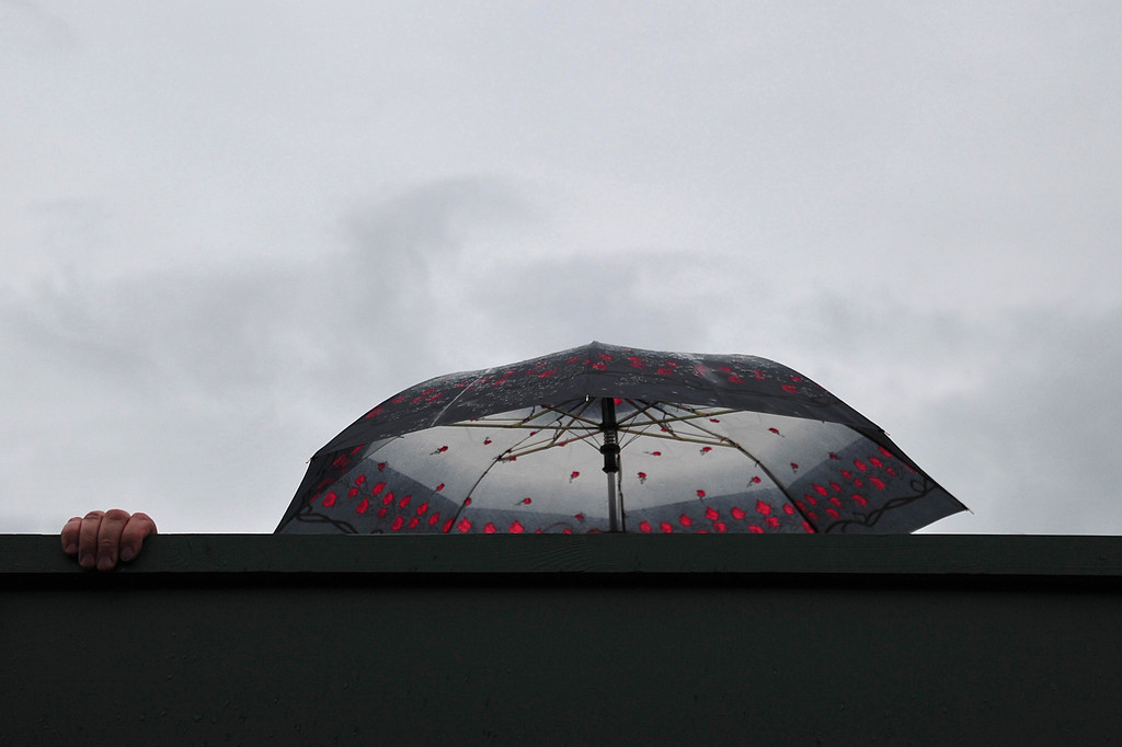 . A spectator shelters under an umbrella after rain interrupted play on day eight of the 2013 Wimbledon Championships tennis tournament at the All England Club in Wimbledon, southwest London, on July 2, 2013. CARL COURT/AFP/Getty Images