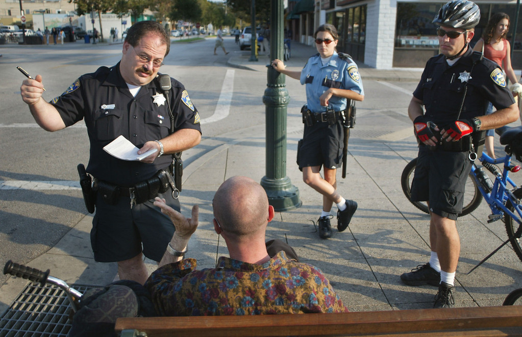 . In this 2002 file photo, Santa Cruz police Sgt. Loran Baker, left, writes a traffic citation for a bicyclist who ran a stop sign on Pacific Avenue in Santa Cruz. Community Service Officer Kayla Gray and officer Derrick Phelps look on. (Patrick Tehan/Media News file)
