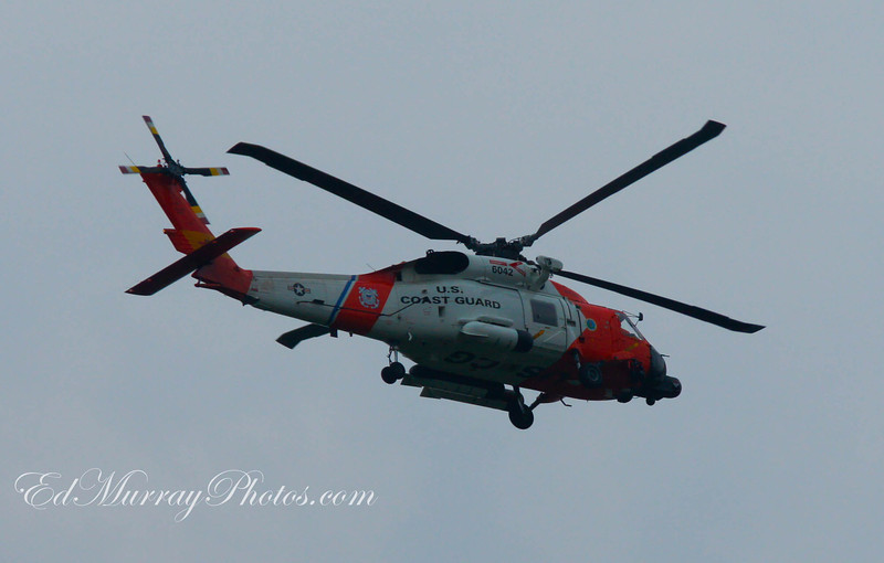 """Low Fly By: (I took this a little while ago.)  I was home watching the Red Sox when I heard this incredible roar and my house started to shake. I grabbed my camera, blasted through my front door and started firing away like a lunatic at this Coast Guard helicopter which flew over my house. The copter flew over the trees and disappeared. I went back in and sat down in front of the tv. A moment later my neighbor called me and said """"What the hell was that???? I saw a helicopter fly over, then you blew through your front door and opened fire on it like we were under attack then it was all over!!!"""" That was the craziest thing I've seen in a long time. I'm glad that camera wasn't a gun"""""""