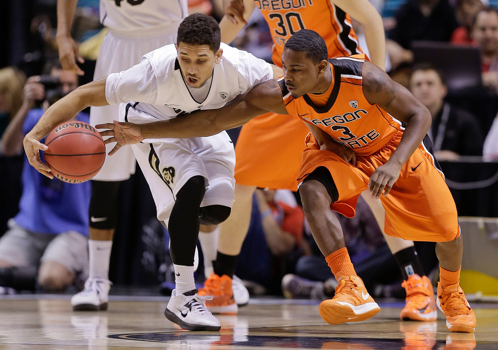 . Colorado\'s Askia Booker, left, keeps the ball away from Oregon State\'s Ahmad Starks during the first half of a Pac-12 Conference tournament NCAA college basketball game, Wednesday, March 13, 2013, in Las Vegas. (AP Photo/Julie Jacobson)