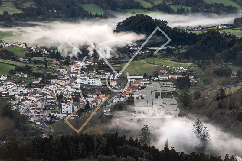 Village of Furnas at sunrise with a fog mist of gases and steams from several fumaroles, calderas and thermal pools.