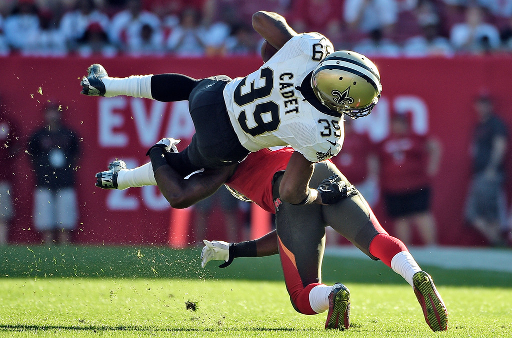 . New Orleans Saints running back Travaris Cadet is sent flying on a tackle by Tampa Bay Buccaneers defensive back C.J. Wilson (41) during the fourth quarter of an NFL football game Sunday, Dec. 28, 2014, in Tampa, Fla. (AP Photo/Phelan M. Ebenhack)