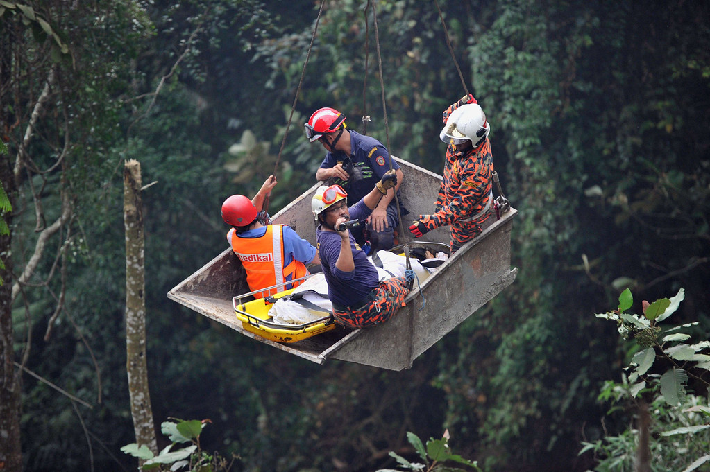 . Malaysian emergency services personnel rescue a passenger (C) after a bus carrying tourists and local residents fell into a ravine near the Genting Highlands, about an hour\'s drive from Kuala Lumpur on August 21, 2013. The bus carrying up to 45 people plunged into a deep ravine near the Malaysian mountaintop tourist resort, police said, but added they could not yet confirm any casualties.       AFP PHOTOSTR/AFP/Getty Images
