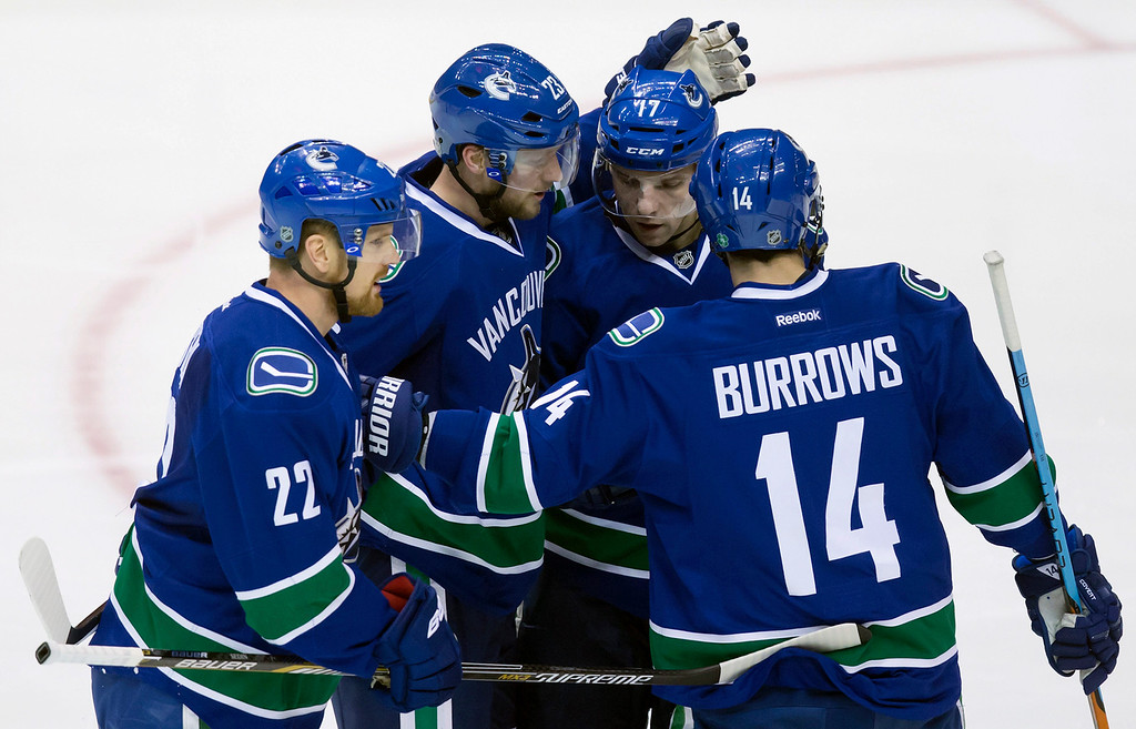 . Vancouver Canucks\' Daniel Sedin, of Sweden, from left, Alexander Edler, of Sweden, Radim Vrbata, of the Czech Republic, and Alex Burrows celebrate Edler\'s goal against the Detroit Red Wings during the second period of an NHL hockey game in Vancouver, British Columbia on Saturday, Jan. 3, 2015. (AP Photo/The Canadian Press, Darryl Dyck)