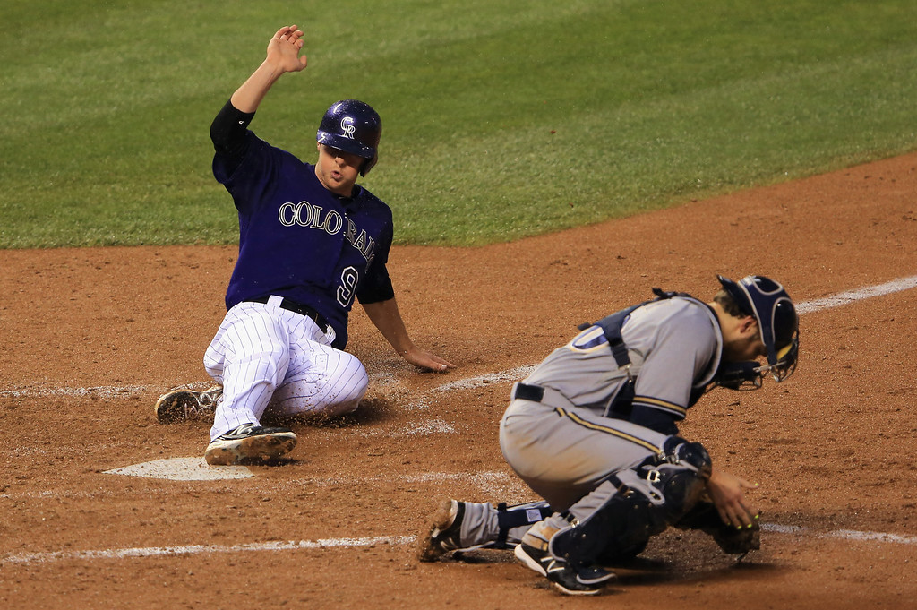 . DENVER, CO - JULY 27:  DJ LeMahieu #9 of the Colorado Rockies slides home to score behind catcher Jonathan Lucroy #20 of the Milwaukee Brewers in the sixth inning at Coors Field on July 27, 2013 in Denver, Colorado.  (Photo by Doug Pensinger/Getty Images)