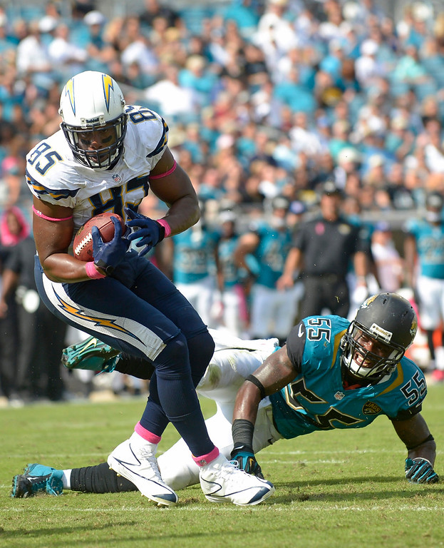 . San Diego Chargers tight end Antonio Gates (85) runs the ball as Jacksonville Jaguars\' Geno Hayes (55) defends during the second half of an NFL football game in Jacksonville, Fla., Sunday, Oct. 20, 2013. (AP Photo/Phelan M. Ebenhack)