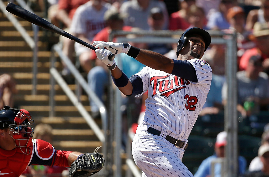. Minnesota Twins\' Aaron Hicks follows through on a swing as Boston Red Sox catcher A.J. Pierzynski, left, looks on in the second inning of an exhibition baseball game, Saturday, March 1, 2014, in Fort Myers, Fla. The Twins beat the Red Sox 6-2. (AP Photo/Steven Senne)