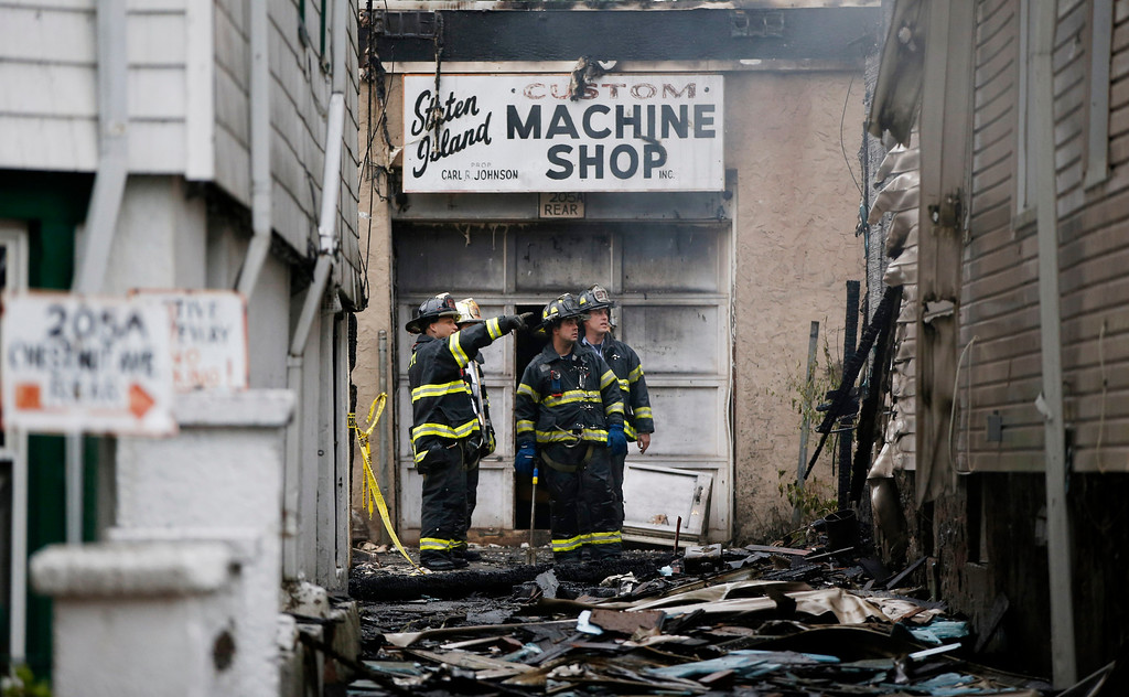 . Firefighters survey damage to the rear of a two-story townhouse at 205 Chestnut Avenue in the Staten Island borough of New York, Thursday, June 5, 2014, after fire severely damaged three adjacent townhouses on the street. (AP Photo/Kathy Willens)