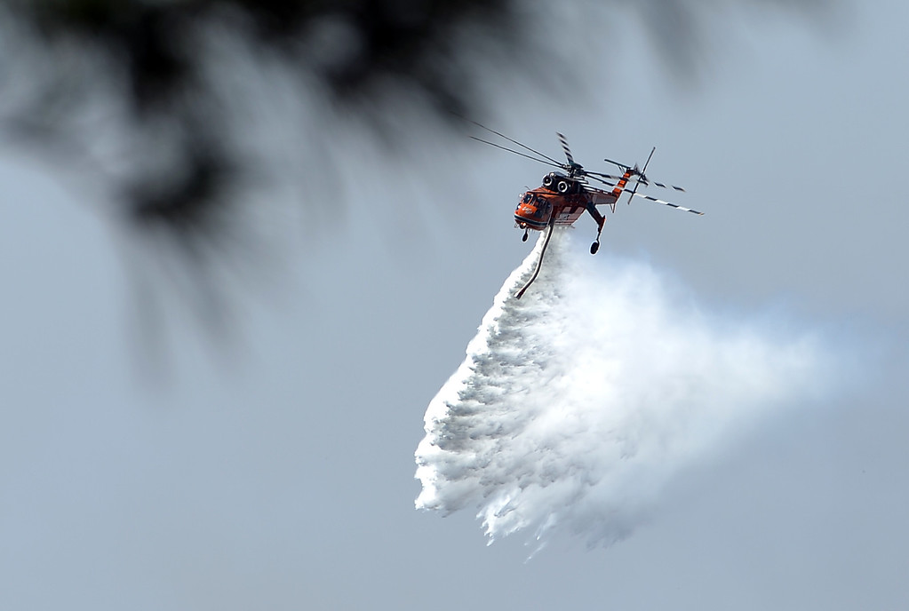 . A helicopter drops water to douse bushfires along the Linksview Road near Faulconbridge in the Blue Mountains on October 23, 2013. Firefighters in Australia battled hot, dry winds and soaring temperatures on October 23 as new blazes began breaking out in a week-long bushfire disaster that shows no signs of easing.  AFP PHOTO/  Saeed KHANSAEED KHAN/AFP/Getty Images