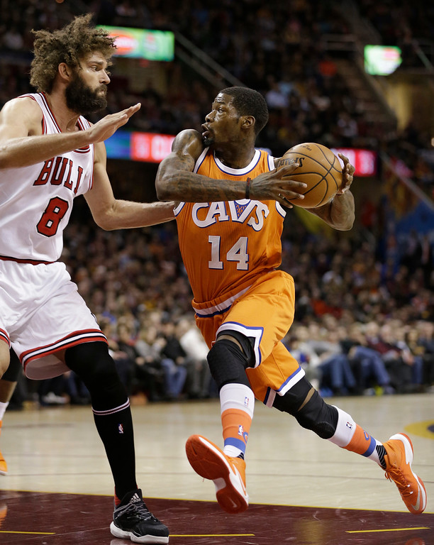 . Cleveland Cavaliers\' DeAndre Liggins (14) drives against Chicago Bulls\' Robin Lopez (8) in the first half of an NBA basketball game, Wednesday, Jan. 4, 2017, in Cleveland. (AP Photo/Tony Dejak)