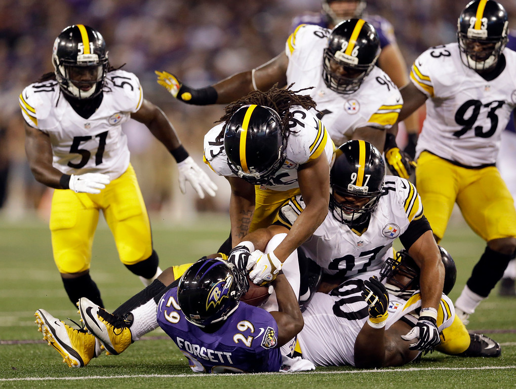 . Baltimore Ravens running back Justin Forsett (29) is tackled by several Pittsburgh Steelers, including outside linebacker Jarvis Jones (95), defensive end Cameron Heyward (97) and nose tackle Steve McLendon (90), during the first half of an NFL football game Thursday, Sept. 11, 2014, in Baltimore. (AP Photo/Patrick Semansky)