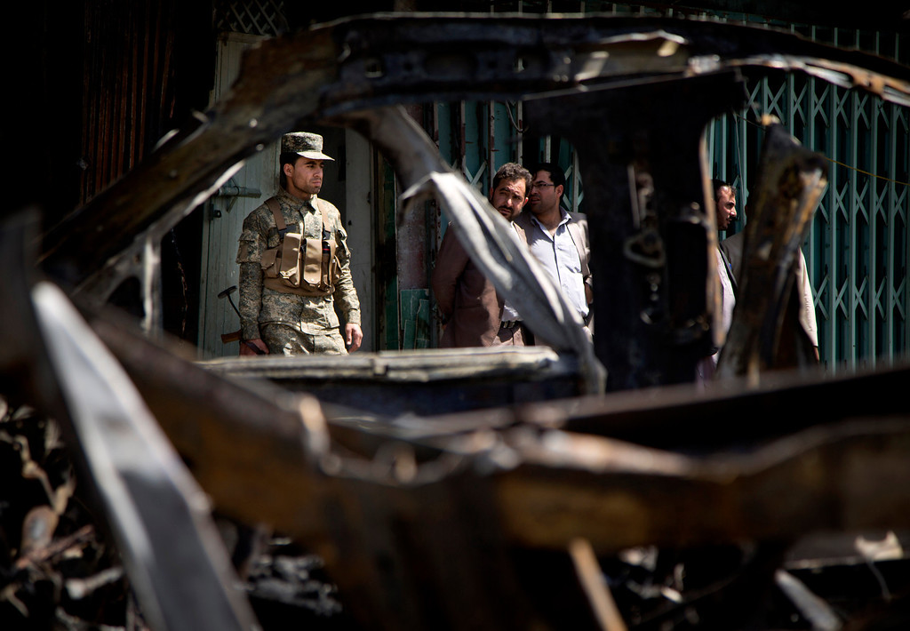 . An Afghan Army soldier is seen through the wreckage of a destroyed car after a suicide car bomber attacked a NATO convoy in Kabul, Afghanistan, Thursday, May 16, 2013.  (AP Photo/Anja Niedringhaus)