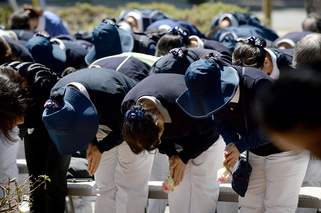 . Tzu Chi Foundation volunteers bow to offer their respects during a prayer ceremony for the Asiana Flight victims put on by the Tzu Chi Foundation in Burlingame, Calif., on Saturday, July 13, 2013. Tzu Chi is an international Buddhist relief organization that began in Taiwan and offers compassionate efforts for charity, medical treatment, education and disaster relief.  (Dan Honda/Bay Area News Group)