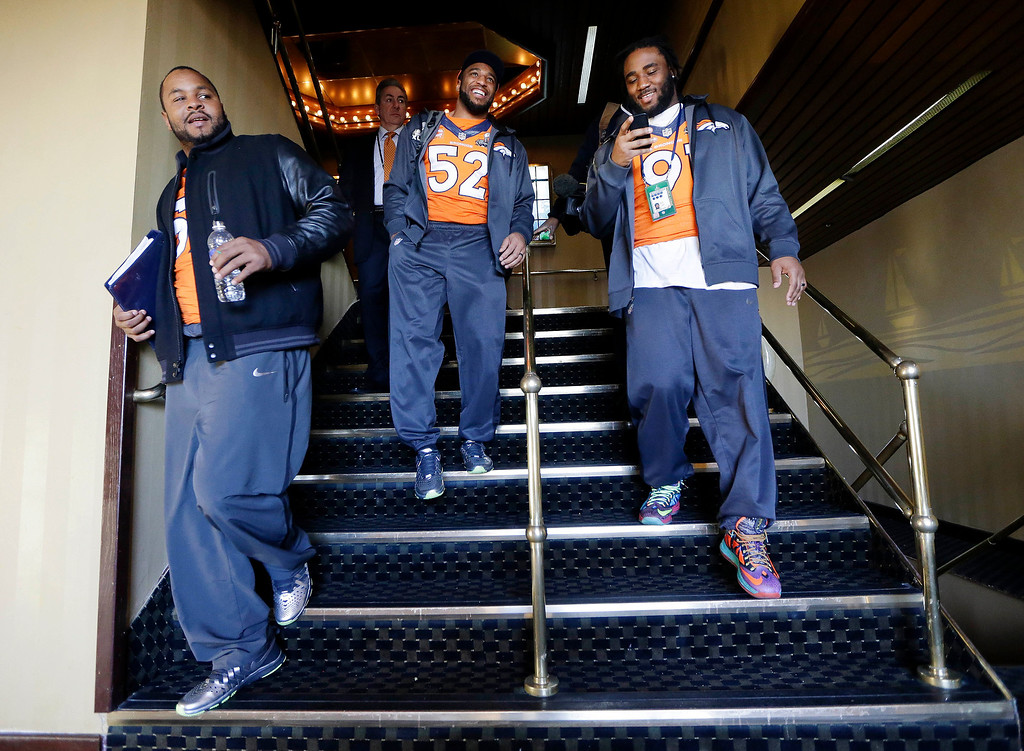 . Denver Broncos defensive end Jeremy Mincey, left, linebacker Wesley Woodyard (52) and defensive end Robert Ayers, right, leave the cruise ship where the team\'s daily news conference was held Thursday, Jan. 30, 2014, in Jersey City, N.J. The Broncos are scheduled to play the Seattle Seahawks in the NFL Super Bowl XLVIII football game Sunday, Feb. 2, in East Rutherford, N.J. (AP Photo)