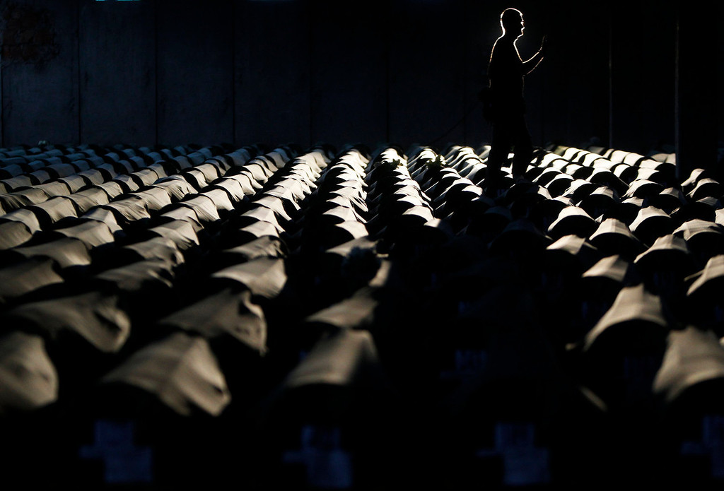 . A Bosnian man walks near the 409 coffins of newly identified victims of the 1995 Srebrenica massacre in Potocari Memorial Center, near Srebrenica July 9, 2013. The bodies of the recently identified victims will be buried on July 11 marking the 18th anniversary of the massacre in which Bosnian Serb forces commanded by Ratko Mladic killed up to 8,000 Muslim men and boys and buried them in mass graves. REUTERS/Dado Ruvic