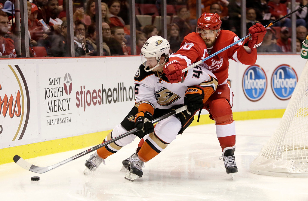 . Detroit Red Wings\' Henrik Zetterberg (40), of Sweden, tries to pull Anaheim Ducks\' Sami Vatanen (45), of Finland, off the puck during the second period of an NHL hockey game Saturday, Oct. 11, 2014, in Detroit. The Ducks defeated the Red Wings 3-2. (AP Photo/Duane Burleson)