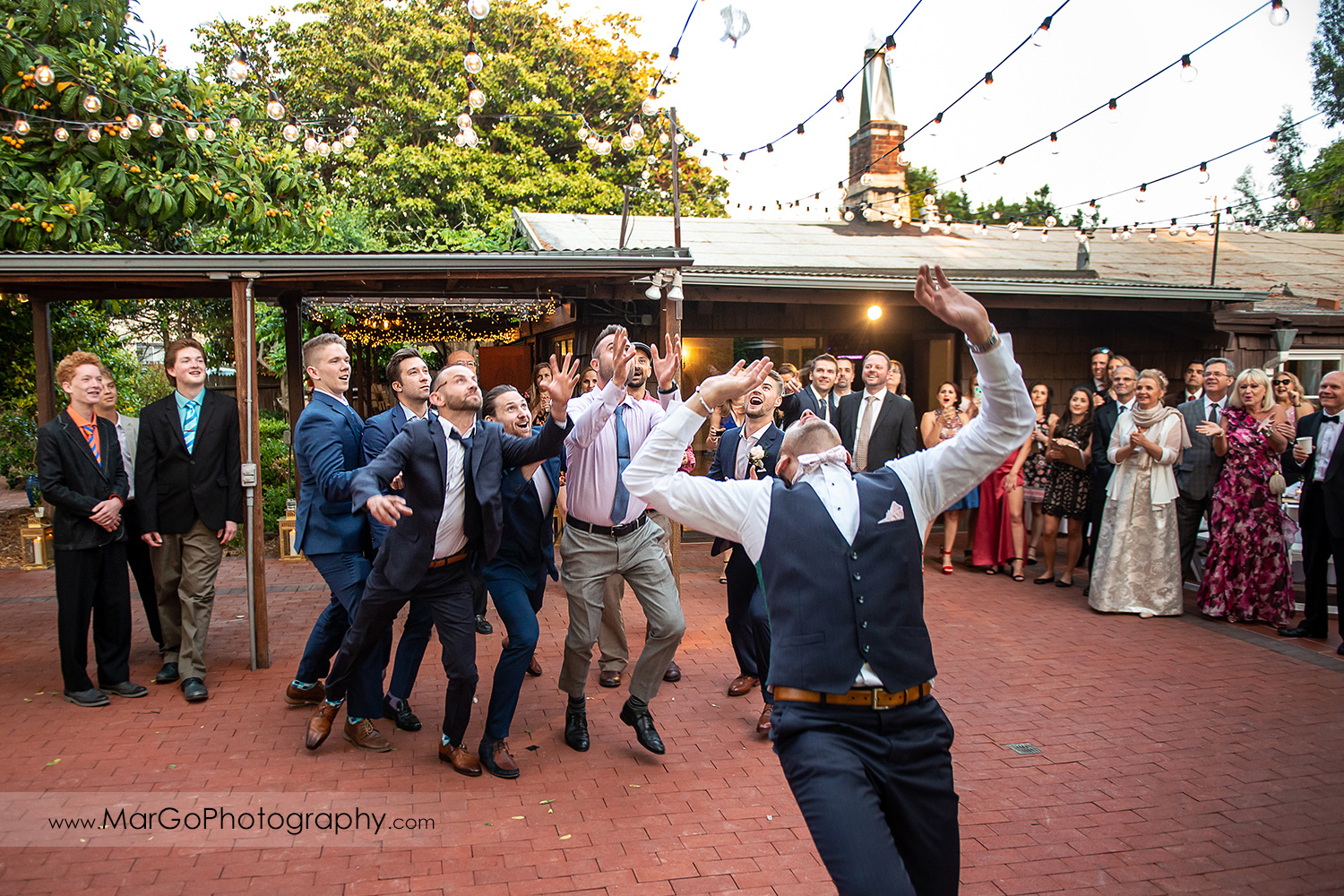 groom tossing garter during wedding reception at San Pablo Rockefeller Lodge