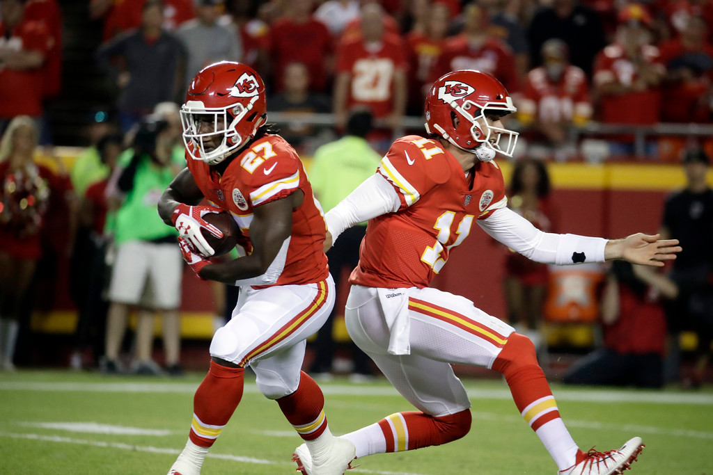 . Kansas City Chiefs running back Kareem Hunt (27) is handed the ball by quarterback Alex Smith (11) during the first half of an NFL football game against the Washington Redskins in Kansas City, Mo., Monday, Oct. 2, 2017. (AP Photo/Charlie Riedel)