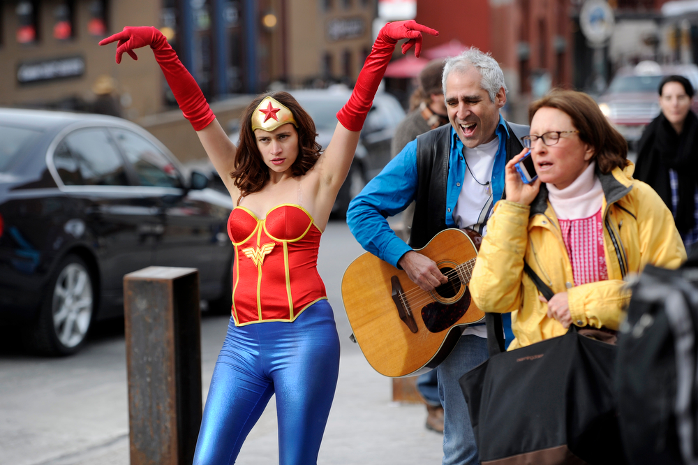 ". Sara Fischel, left, of Los Angeles, an actress and filmmaker working on a film called ""The Adventures of Wonder Woman,\"" dances along with street musician Stewart Antelis, center, on Main Street during the seventh day of the 2014 Sundance Film Festival, on Wednesday, Jan. 22, 2014, in Park City, Utah. (Photo by Chris Pizzello/Invision/AP)"