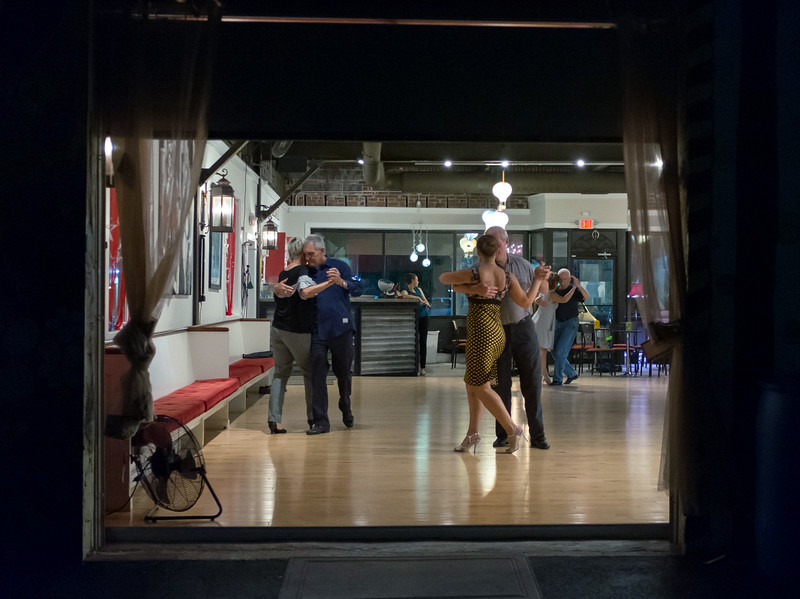 06/27/18  Wesley Bunnell | Staff  With the rear bay door open for the warm weather students Lynn and Richard Ladisky, L, tango dance as the owner and instructor of the Garage Dance Studio Muna Swairjo, middle, dances with Paul Hoar.
