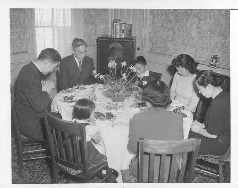 """""""They're Japanese -- but loyal Americans.  The Tsukamotos bow their heads as the Rev. Joseph K. Tsukamoto, left, pastor of the Protestant Episcopal Christ Church, says grace and prays for the safety of America.""""--caption on photograph"""