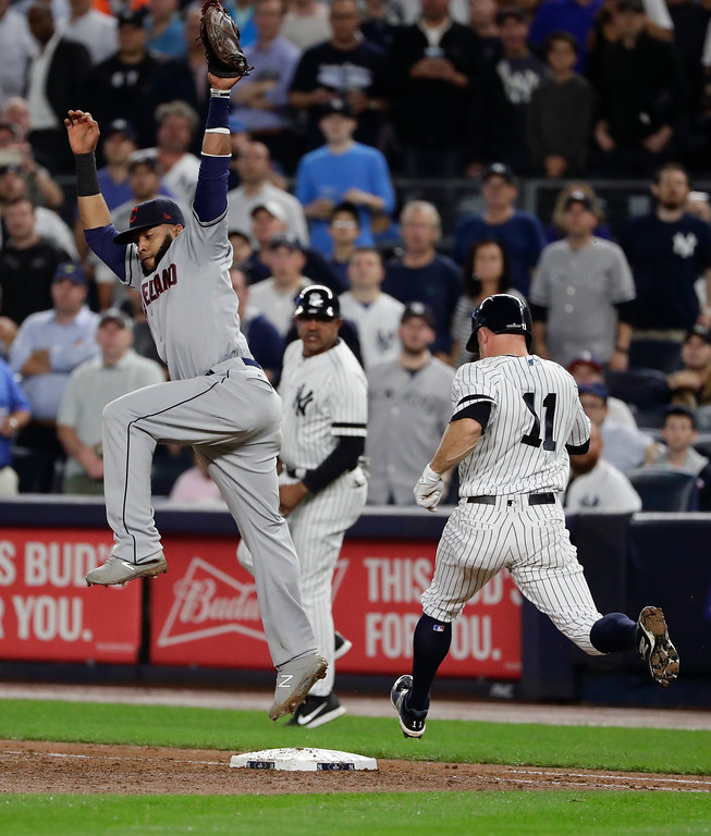 . New York Yankees\' Brett Gardner (11) reaches first base safely as Cleveland Indians first baseman Carlos Santana leaps for the throw from third baseman Giovanny Urshela during the third inning in Game 4 of baseball\'s American League Division Series, Monday, Oct. 9, 2017, in New York. Starlin Castro scored on the play. (AP Photo/Frank Franklin II)