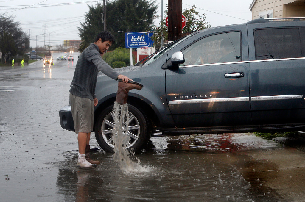 . Johnny Ochoa empties his boot while helping place sandbags around the Maria Elena restaurant on Gold Street in Alviso, Calif., on Thursday afternoon, Dec. 11, 2014. (Karl Mondon/Bay Area News Group)