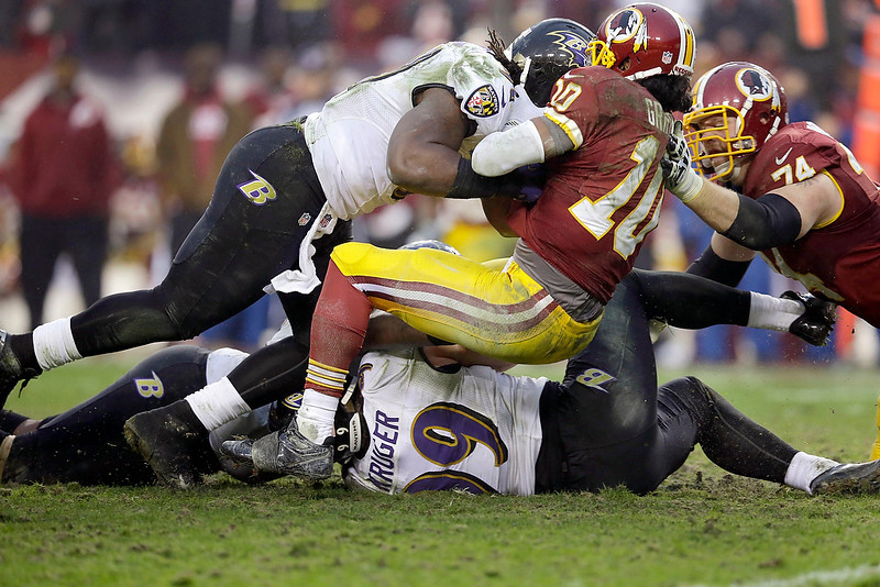 . Washington Redskins quarterback Robert Griffin III is sacked by Baltimore Ravens outside linebacker Courtney Upshaw (91) and outside linebacker Paul Kruger (99) during the second half of an NFL football game in Landover, Md., Sunday, Dec. 9, 2012. (AP Photo/Alex Brandon)