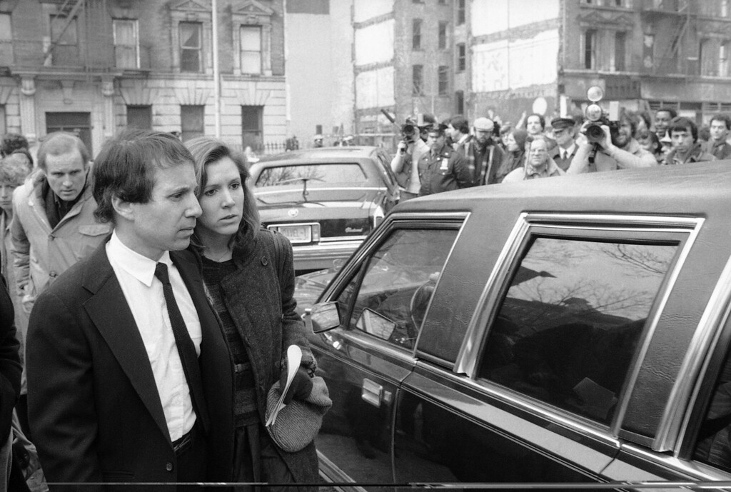 . Composer and singer Paul Simon and actress Carrie Fisher pose outside of Simon\'s Manhattan apartment in New York, Aug. 17, 1983, after the couple were married in a private ceremony. The two tied the knot after a five-year romance. (AP Photo/Mario Suriani)
