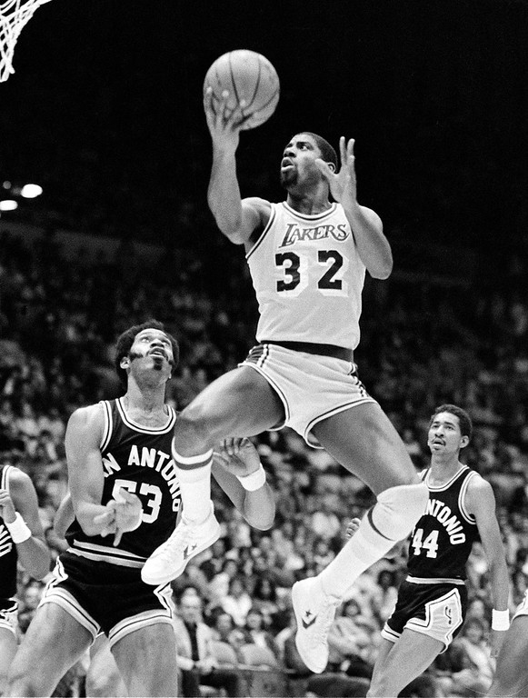 . ** FILE ** In this March 25, 1983, file photo, Los Angeles Lakers\' Macic Johnson (32) leaps high over San Antonio Spurs defenders Artis Gilmore (53) and George Gervin (44) during an NBA basketball game in Los Angeles. The Lakers and the Boston Celtics, who have combined to win 30 of 61 championships, are squaring off in the NBA finals for the 11th time and first since 1987. (AP Photo)
