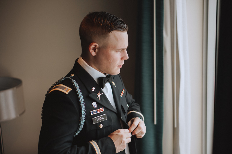 Groom buttoning his jacket.