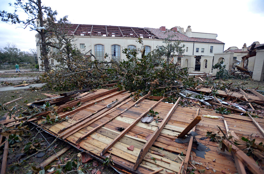 . Debris sits near the damaged auditorium building at Murphy High School as residents clean up and assess the damage from a Christmas Day tornado Wednesday, Dec. 26, 2012  in Mobile, Ala. With only a handful of injuries and no deaths reported statewide from the storms, the head of the state\'s emergency response said it was difficult to fathom how the toll wasn\'t worse. (AP Photo/G.M. Andrews)