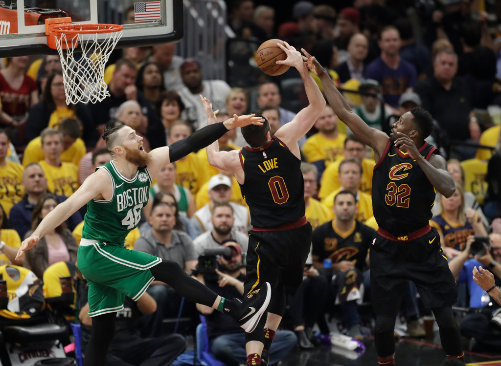 . Cleveland Cavaliers\' Kevin Love (0) controls a rebound in front of Boston Celtics\' Aron Baynes (46), from Australia, and Cavaliers\' Jeff Green in the second half of Game 3 of the NBA basketball Eastern Conference finals, Saturday, May 19, 2018, in Cleveland. (AP Photo/Tony Dejak)