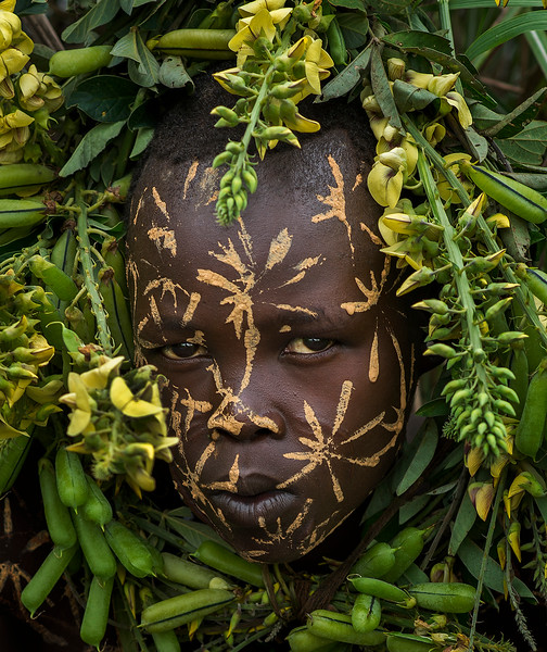A Suri boy blends into the background with the traditional body painting.   Suri, Ethiopia, 2017