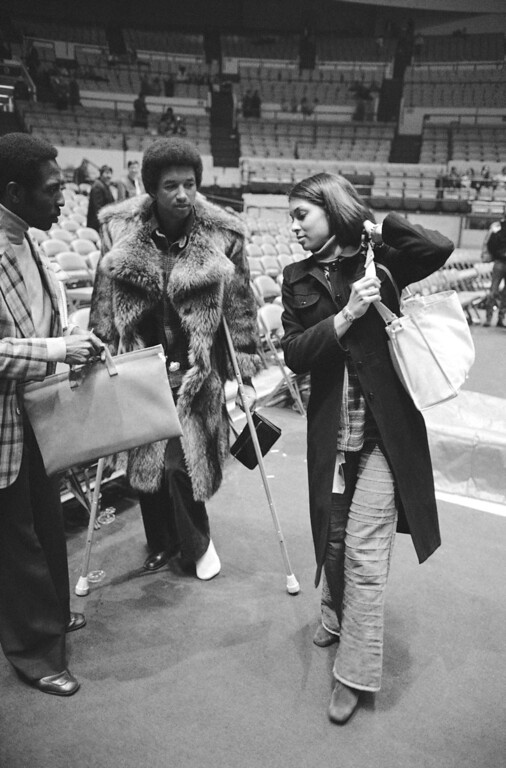 . Arthur Ashe, left, tennis star, and his fiance, Jeanne Moutoussamy leave New York\'s Madison Square Garden on Wednesday, Feb. 16, 1977 following the New York-Chicago basketball game. Ashe went to watch the game and Jeanne took pictures. She is from Chicago and is a freelance photographer in New York where she works at WNBC, an affiliate station in N.Y. for NBC. They will be married on Sunday at the United Nations Chapel by U.N. Ambassador, Andrew Young, a friend of the couple. (AP Photo/Carlos Rene Perez)