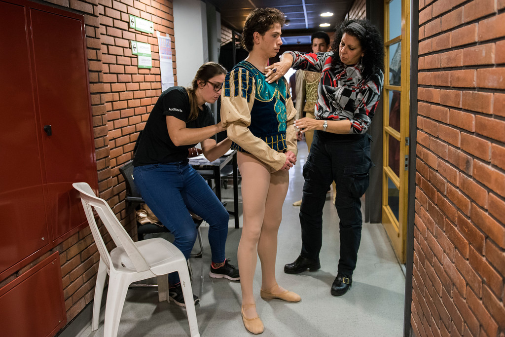 . In this Tuesday, Sept. 19, 2017 photo, principal dancer Ciro Tamayo is helped by costume assistants before a dress rehearsal of Romeo and Juliet in Montevideo, Uruguay.  Argentine ballet great Julio Bocca retired a decade ago after a brilliant quarter-century run but he has kept the same passion that he performed on some of the most famous stages to lift the Uruguayan company by attracting prestigious choreographers, instructors and international and local dancers. (AP Photo/Matilde Campodonico)
