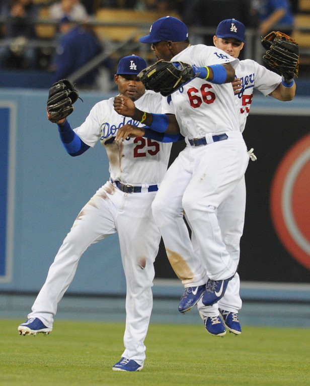 . Dodgers Carl Crawford, Yasiel Puig and Skip Schumaker at the end of the game. The Dodgers defeated the New York Mets  4-2 in a game at Dodger Stadium in Los Angeles, CA. 8/13/2013(John McCoy/LA Daily News)