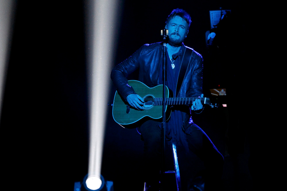 """. Eric Church is bathed in blue light as he performs \""""Like Jesus Does\"""" at the 48th ACM Awards in Las Vegas, April 7, 2013.  REUTERS/Mario Anzuoni"""