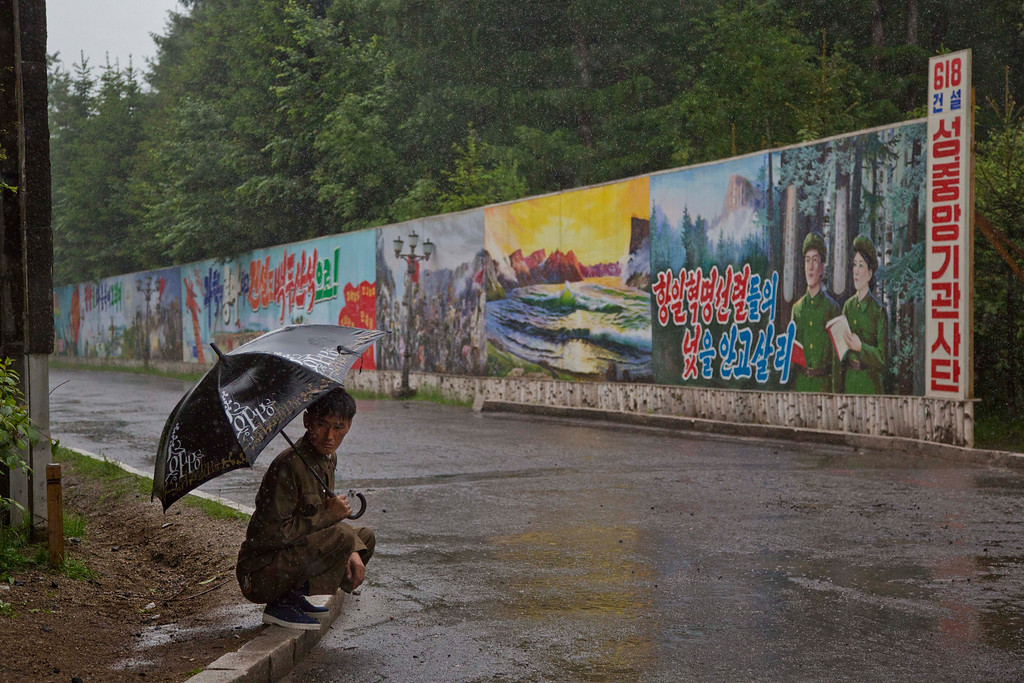 """. In this June 17, 2014 photo, a North Korean man takes shelter in the rain next to long propaganda billboards in the town of Samjiyon in North Korea\'s Ryanggang province. The Associated Press was granted permission to embark on a weeklong road trip across North Korea to the countryís spiritual summit Mount Paektu. The trip was on North Korea\'s terms. An AP reporter and photographer couldn\'t interview ordinary people or wander off course, and government \""""minders\"""" accompanied them the entire way. (AP Photo/David Guttenfelder)"""