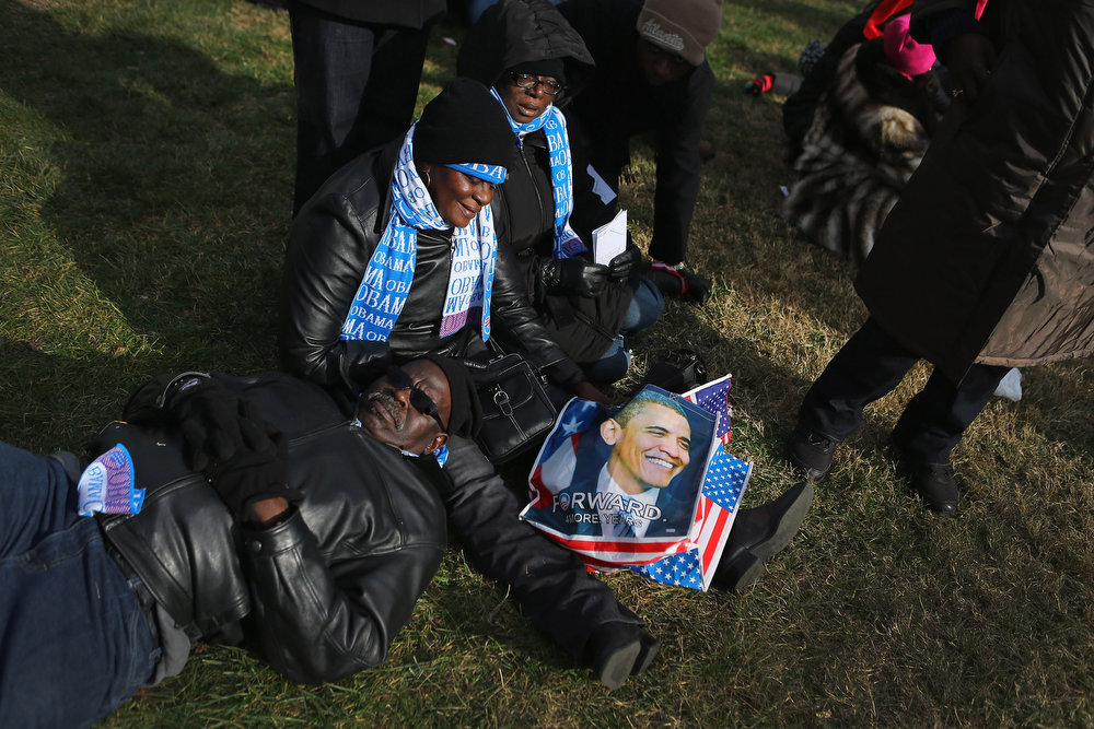 . People lie and sit on the ground as they gather near the U.S. Capitol building on the National Mall for the Inauguration ceremony on January 21, 2013 in Washington, DC.  U.S. President Barack Obama will be ceremonially sworn in for his second term today.  (Photo by Joe Raedle/Getty Images)