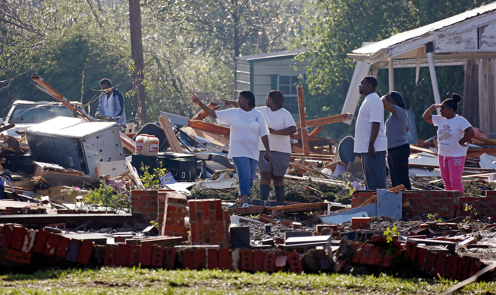 . Friends and relatives search through the remains of a child care center in Louisville, Miss., Tuesday, April 29, 2014. The facility and the auto repair shop next door were demolished by a tornado Monday. (AP Photo/Rogelio V. Solis)