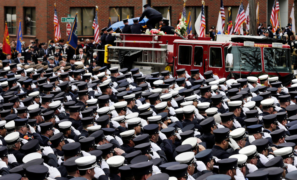 . Firefighters salute as the casket of Boston fire Lt. Edward Walsh is lowered from Engine 33 as the funeral procession arrives outside St. Patrick\'s Church in Watertown, Mass., Wednesday, April 2, 2014. Walsh and his colleague Michael Kennedy died after being trapped while battling a nine-alarm apartment fire in Boston on March 26. (AP Photo/Charles Krupa)