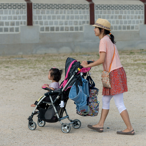 Mother pushing her daughter in a baby stroller, Seoul, South Korea