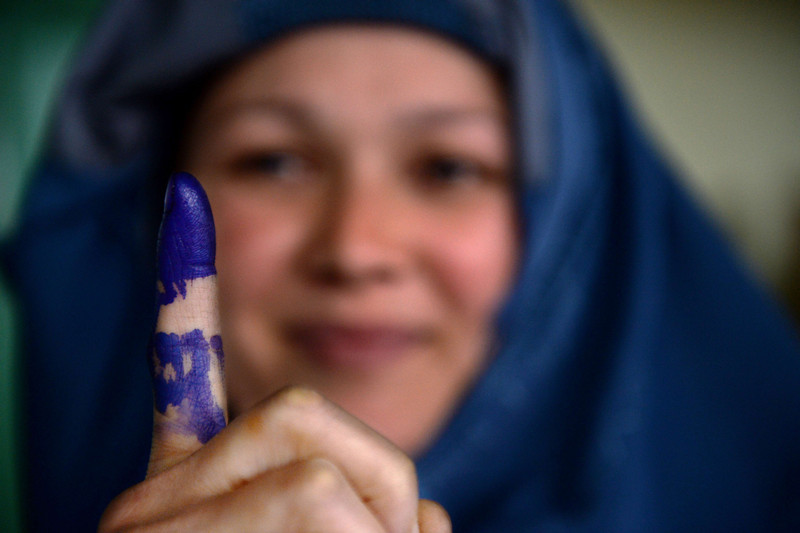. An Afghan voter shows her inked finger after she cast her ballot at a local polling station in Kabul on April 5, 2014. Afghan voters went to the polls to choose a successor to President Hamid Karzai, braving Taliban threats in a landmark election held as US-led forces wind down their long intervention in the country. Afghanistan\'s third presidential election brings an end to 13 years of rule by Karzai, who has held power since the Taliban were ousted in a US-led invasion in 2001, and will be the first democratic handover of power in the country\'s turbulent history.  (SHAH MARAI/AFP/Getty Images)