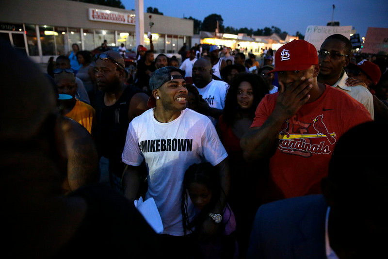 . Rapper Nelly, center, walks the streets with protesters Monday, Aug. 18, 2014, in Ferguson, Mo. The Aug. 9 shooting of Michael Brown by police has touched off rancorous protests in Ferguson, a St. Louis suburb where police have used riot gear and tear gas and Gov. Jay Nixon ordered the National Guard to help restore order Monday. (AP Photo/Jeff Roberson)