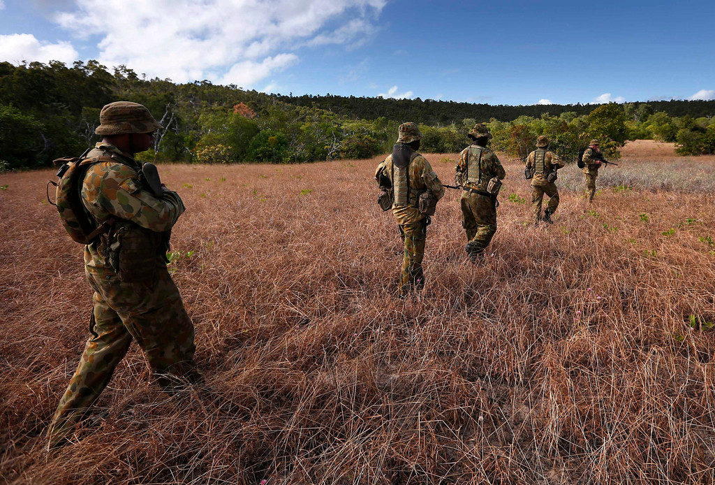 . Indigenous soldiers from Australia\'s North West Mobile Force (NORFORCE) unit, walk in formation during a surveillance and reconnaissance patrol around Astell Island, part of the English Company Islands, located inside Arnhem Land in the Northern Territory July 17, 2013. NORFORCE is a surveillance unit that employs ancient Aboriginal skills to help in the seemingly impossible task of patrolling the country\'s vast northwest coast. NORFORCE\'s area of operations is about 1.8 million square km (700,000 square miles), covering the Northern Territory and the north of Western Australia. Aboriginal reservists make up a large proportion of the 600-strong unit, and bring to bear their knowledge of the land and the food it can provide. Fish, shellfish, turtle eggs and even insects supplement rations during the patrol, which is on the lookout for illegal foreign fishing vessels and drug smugglers, as well as people smugglers from neighboring Indonesia. Picture taken July 17, 2013. REUTERS/David Gray